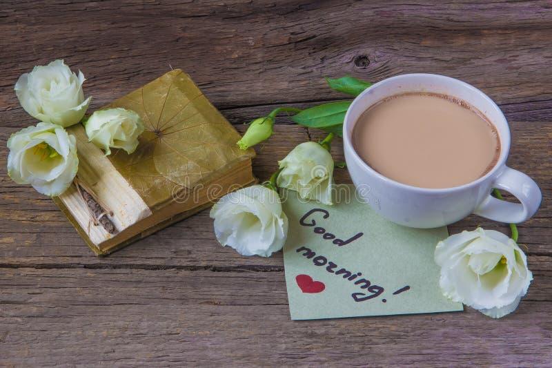 Copo de café com o lisianthus da flor da mola e o bom dia das notas imagens de stock