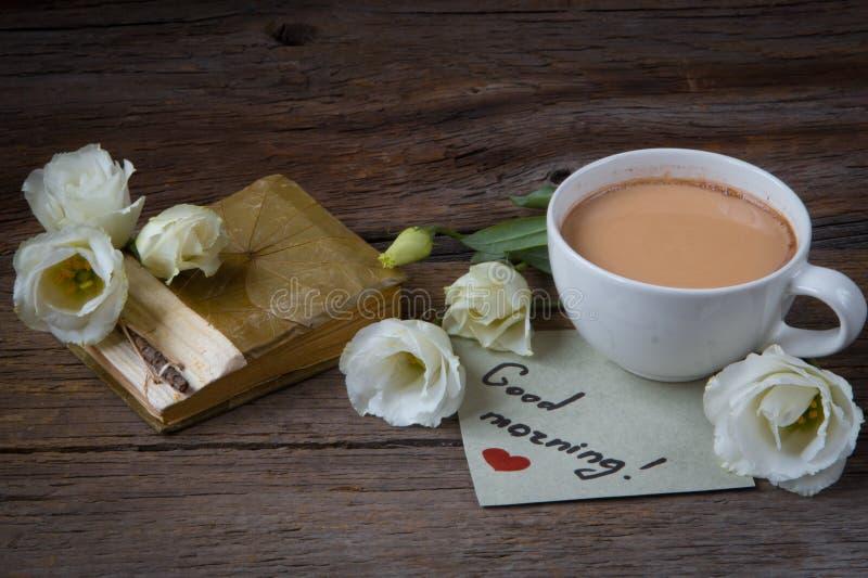 Copo de café com o lisianthus da flor da mola e o bom dia das notas imagem de stock royalty free