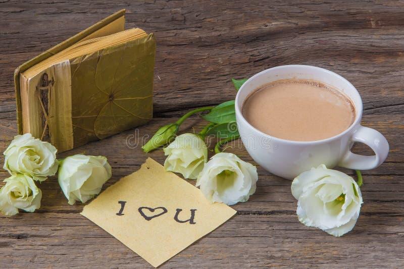 Copo de café com o lisianthus e as notas da flor da mola eu te amo sobre imagem de stock