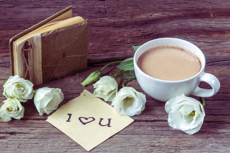 Copo de café com o lisianthus e as notas da flor da mola eu te amo sobre fotografia de stock