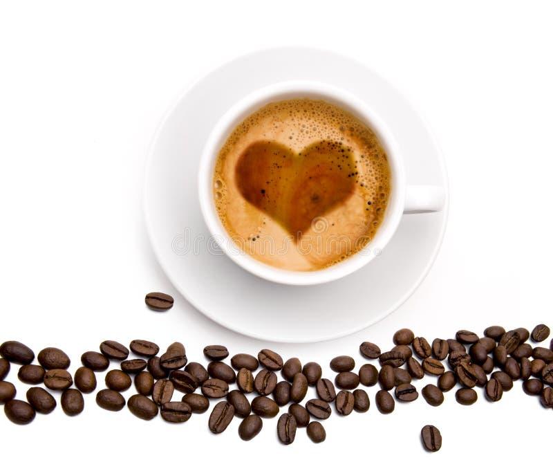 Copo de café com os feijões do haeart e de café fotos de stock royalty free