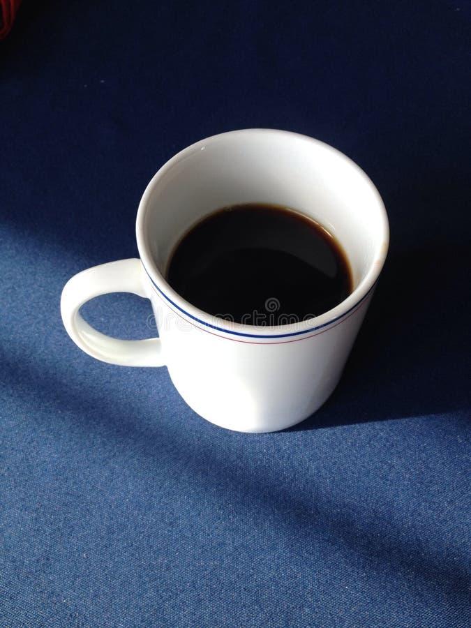 Copo de café com um fundo azul fotos de stock royalty free