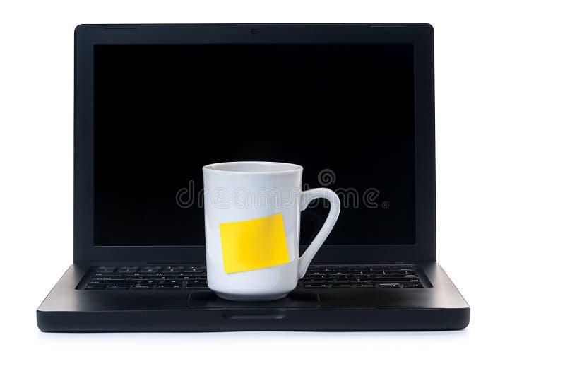 Copo de café com uma nota amarela em um portátil fotos de stock royalty free