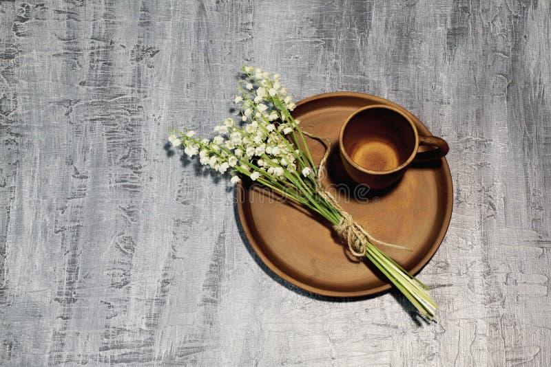 Copo de café da argila e ramalhete de lírios perfumados da floresta do vale amarrado com guita fina da juta no prato cerâmico Bac foto de stock