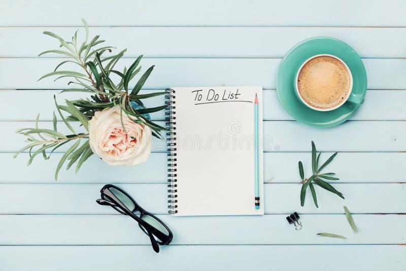 Copo de café da manhã, caderno com para fazer a lista, lápis, monóculos e flor cor-de-rosa do vintage no vaso na tabela rústica a fotos de stock