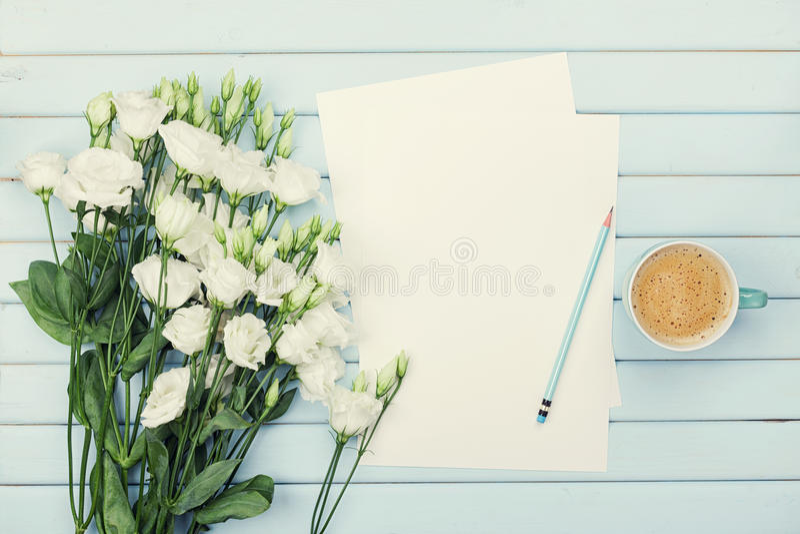 Copo de café da manhã, lista de papel vazia, lápis, e ramalhete do eustoma das flores brancas na tabela rústica azul de cima de M foto de stock royalty free
