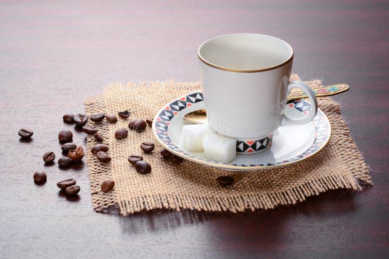 Copo de café da porcelana com pires e a colher dourada em um guardanapo da juta Grupo de café do vintage na tabela de madeira com fotos de stock