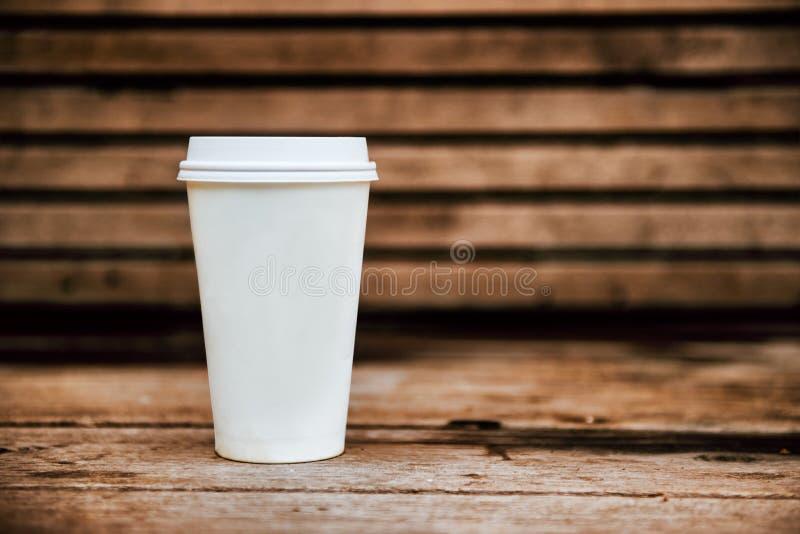 Copo de café de papel da cafetaria no fundo de madeira fotografia de stock