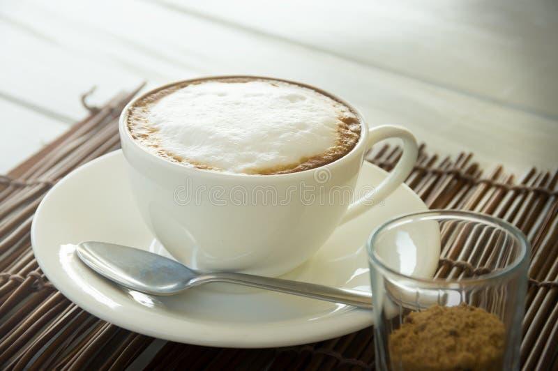 Copo de café do Cappuccino com açúcar marrom imagem de stock