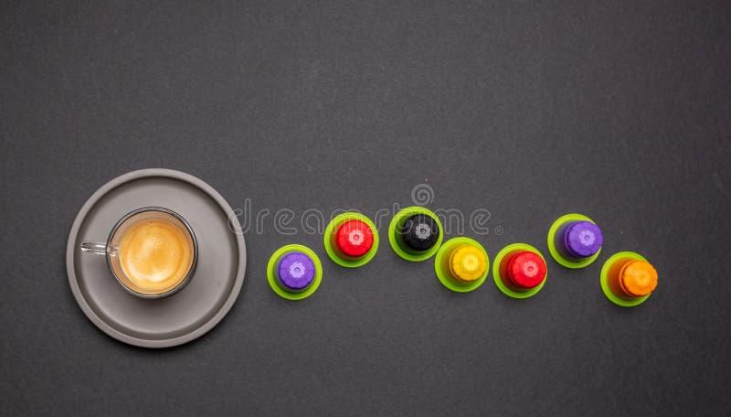 Copo de café do café e cápsulas, vagens, no fundo preto da cor fotos de stock royalty free