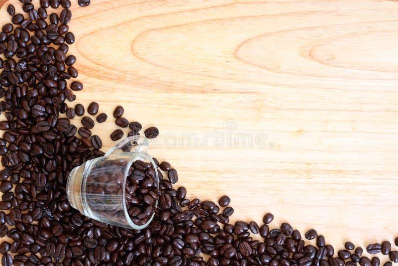 Copo de café do feijão na tabela de madeira imagem de stock