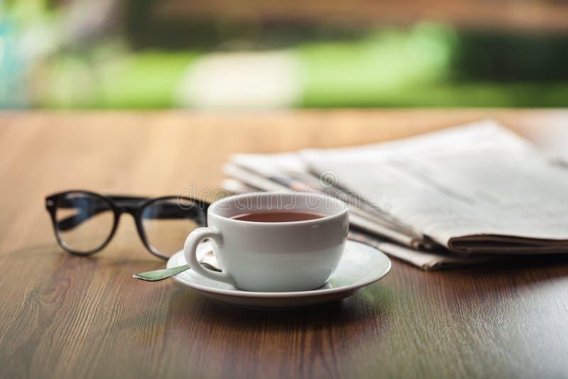 Copo de café dos vidros de leitura do jornal foto de stock royalty free