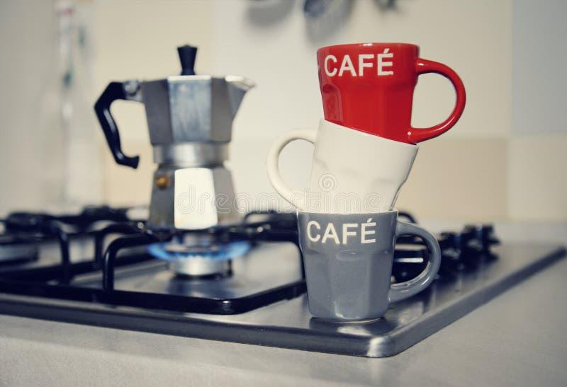 Copo de café e cafeteira empilhados do vintage no fogão de cozinha imagens de stock