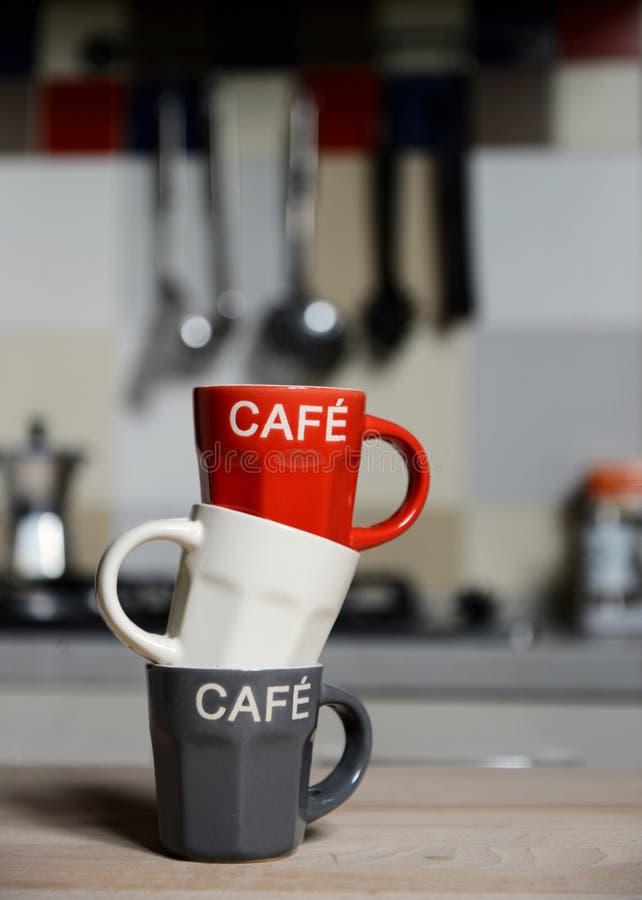Copo de café e cafeteira empilhados do vintage no fogão de cozinha fotografia de stock
