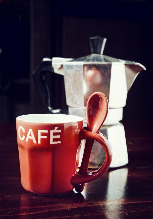 Copo de café e cafeteira vermelhos do vintage na tabela de madeira escura fotos de stock
