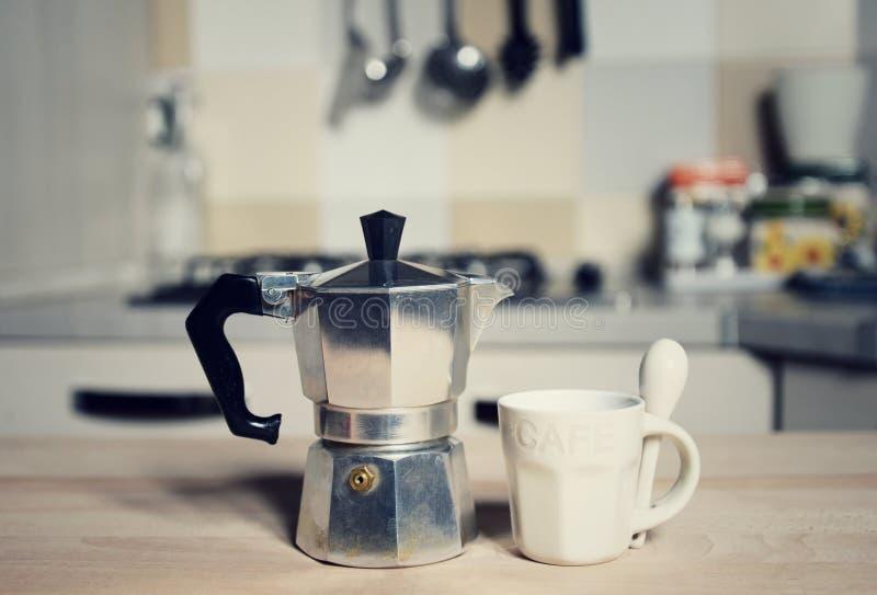 Copo de café e cafeteira vermelhos do vintage no fogão de cozinha fotografia de stock