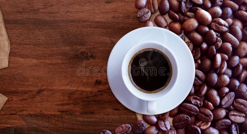 Copo de café e feijões de café no estilo de madeira do vintage do fundo da tabela para o projeto gráfico fotos de stock royalty free