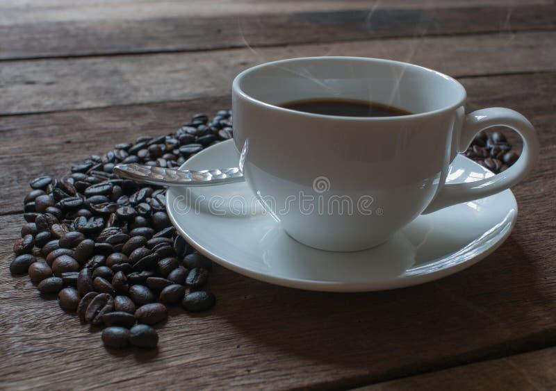 Copo de café e feijões de café no fundo de madeira velho da tabela fotos de stock royalty free