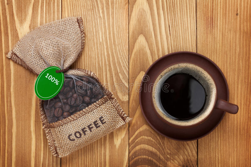 Copo de café e saco pequeno com feijões imagem de stock