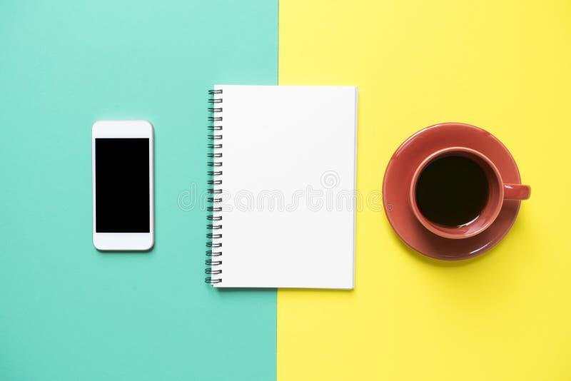 Copo de café, livro de nota, telefone no fundo amarelo e verde imagens de stock royalty free