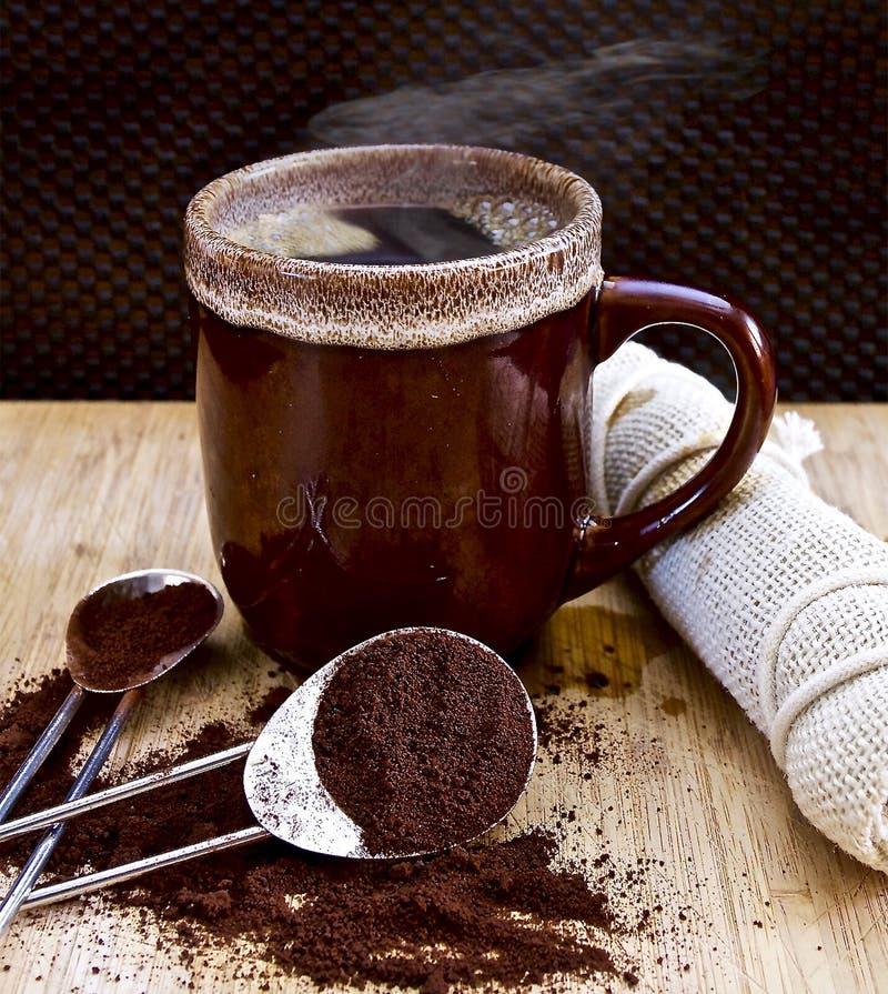 Copo de café marrom dos cocos com terras de café imagens de stock royalty free