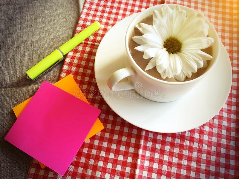 Copo de café na tabela com margarida branca imagem de stock