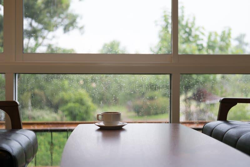 copo de café na tabela de madeira, na cadeira e no sofá de couro marrom perto do vento imagem de stock