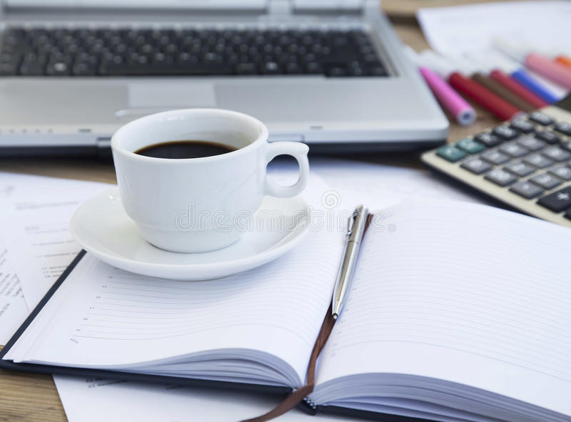 Copo de café no escritório sobre papéis financeiros e agenda Café Bre fotografia de stock royalty free