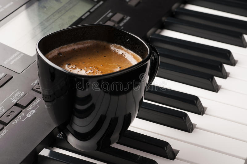 Copo de café no teclado de piano fotografia de stock