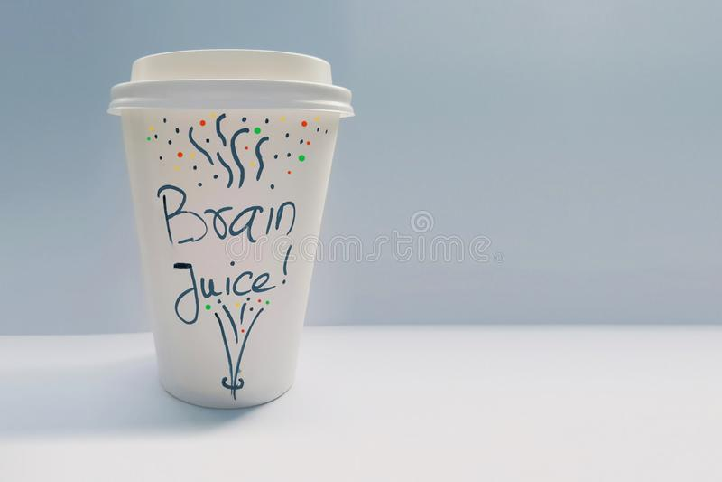 Copo de café de papel descartável branco com as palavras Brain Juice Written nele foto de stock