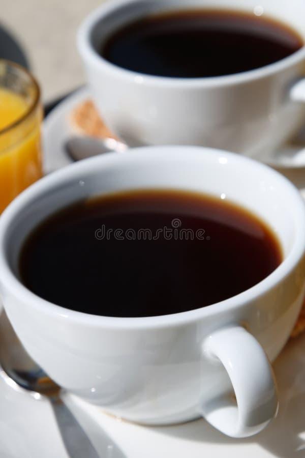 Copo de café preto com outro no fundo imagem de stock royalty free
