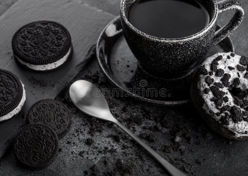 Copo de café preto com pires e filhós com as cookies pretas do sanduíche no fundo de pedra preto da mesa de cozinha Espaço para o imagens de stock