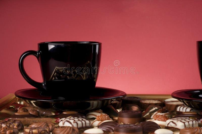 Copo de café preto sobre doces do chocolate. foto de stock