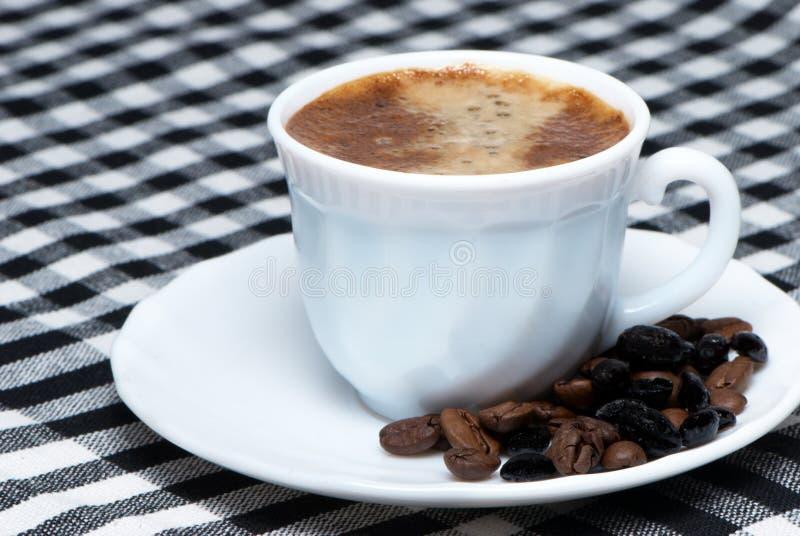 Copo de café sobre feijões de café roasted escuros imagem de stock royalty free