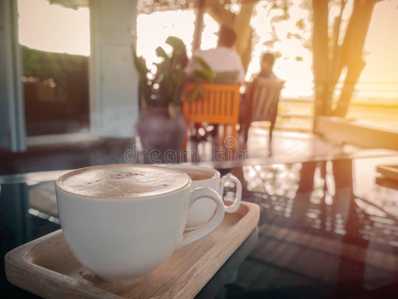 Copo de Cappucino com o copo de chá no restau borrado da cafetaria ou do café imagem de stock