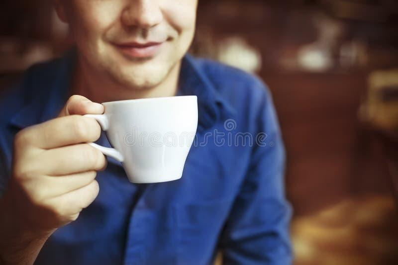 Copo de chá branco bebendo do homem no café imagem de stock