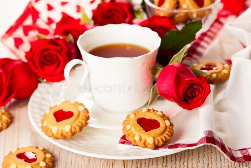 Copo de chá com as cookies para o dia de Valentim imagens de stock