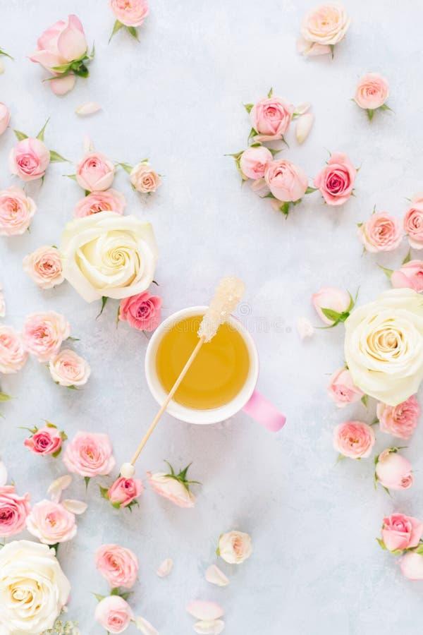 Copo de chá com as rosas sobre fundo textured fotos de stock royalty free