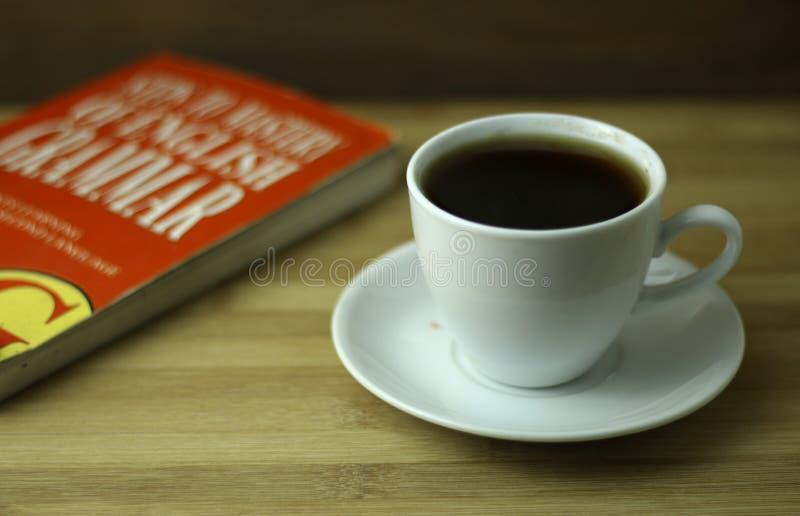 Copo de chá com livro vermelho fotografia de stock royalty free