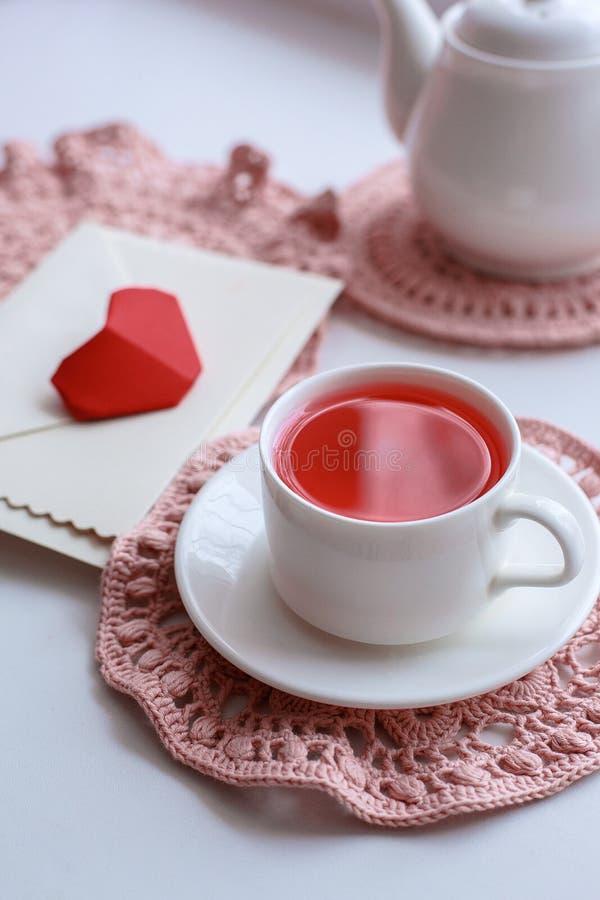 Copo de chá cor-de-rosa scented no guardanapo, no bule e no envelope do crochê na soleira Rosa vermelha Bom dia romance fotografia de stock