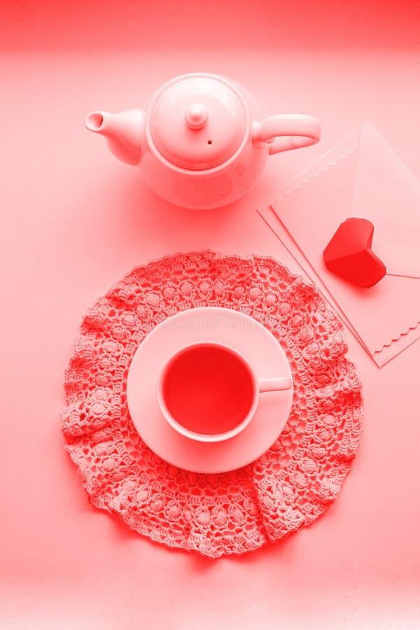 Copo de chá cor-de-rosa scented no guardanapo, no bule e no envelope do crochê na soleira Rosa vermelha Bom dia romance, vivendo fotografia de stock royalty free