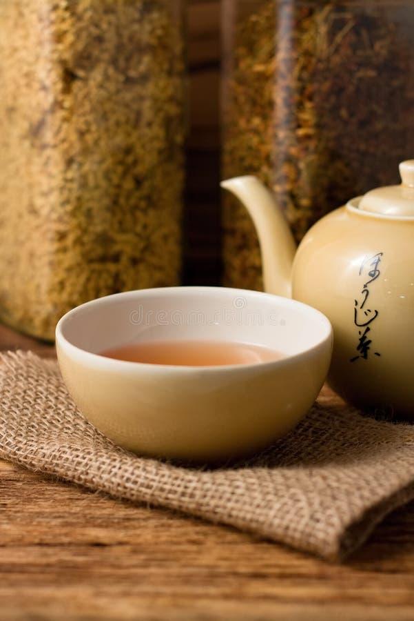 Copo de chá oriental no pano da juta fotos de stock