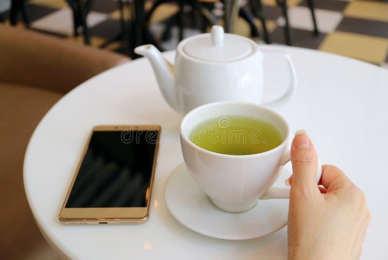 Copo de chá verde quente da terra arrendada da mão da mulher na mesa redonda com bule e Smartphone imagens de stock