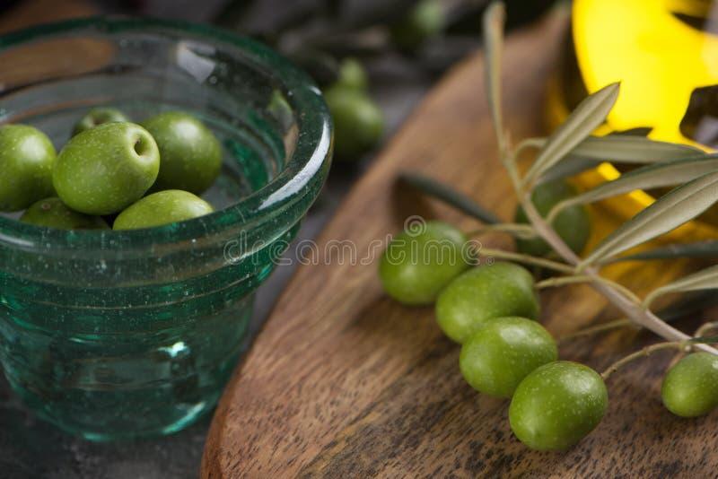 Copo de Glas das azeitonas com azeite virgem extra na garrafa de vidro no fundo rústico Fim acima fotos de stock