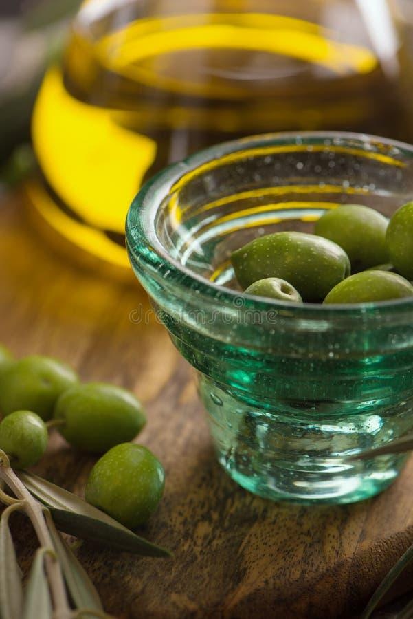 Copo de Glas das azeitonas com azeite virgem extra na garrafa de vidro no fundo rústico Fim acima imagem de stock