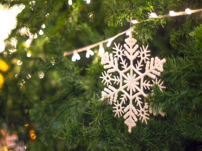 Copo de nieve blanco en la decoración del color verde del árbol de navidad por la iluminación del Año Nuevo con el fondo del boke foto de archivo