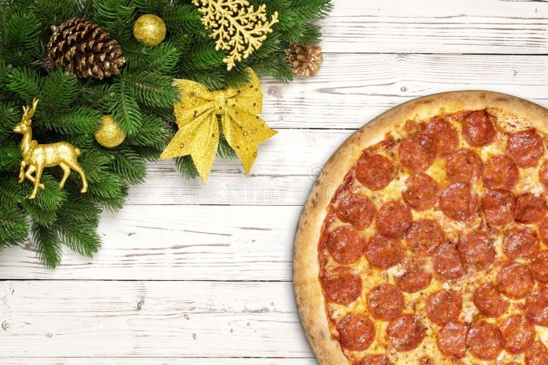 Copo de nieve de la Navidad de los salchichones de la pizza con las ramas del abeto y la bola del juguete del Año Nuevo, ciervos  fotografía de archivo libre de regalías