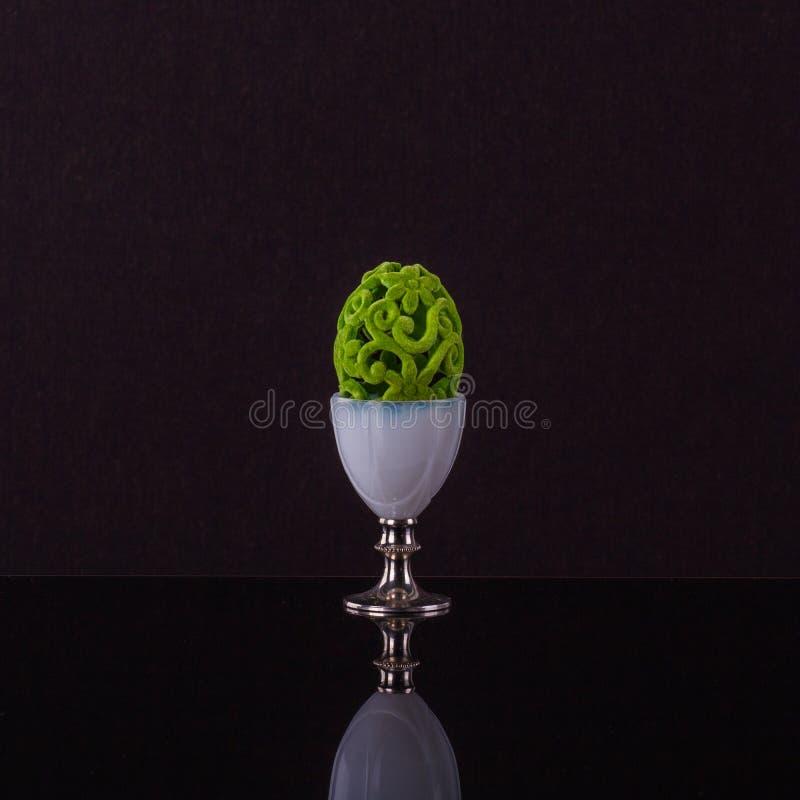 Copo de ovo proeminente com o ovo da páscoa verde fino do elegante foto de stock