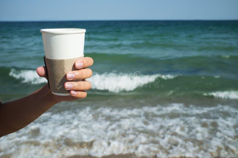 Copo de papel com café à disposição no fundo do mar fotografia de stock