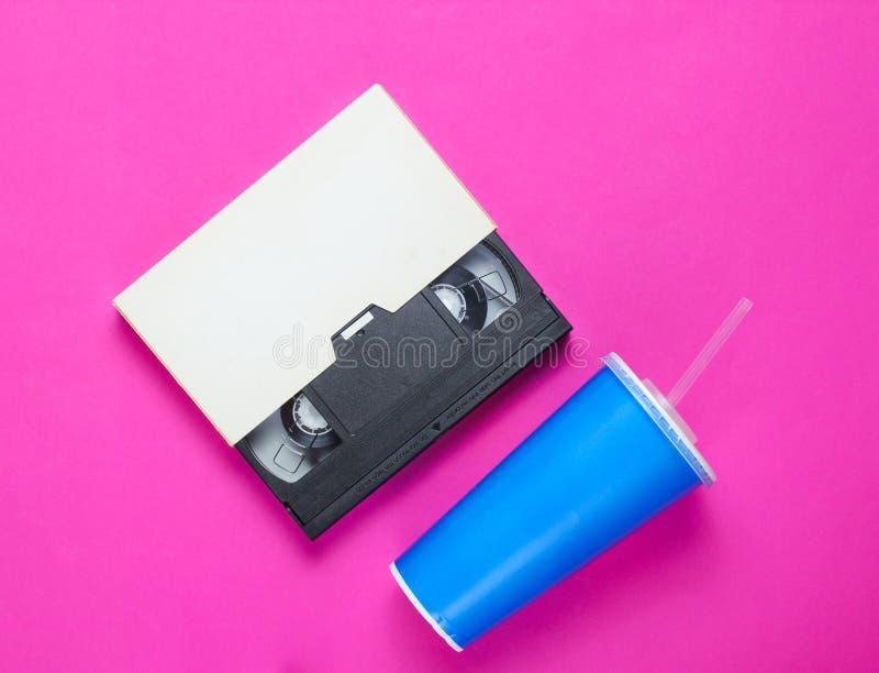 Copo de papel com palha, gaveta video no fundo cor-de-rosa Cultura Pop 80s, estilo retro Vista superior fotografia de stock royalty free